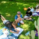 Dzieci podczas lekcji rysunku w parku