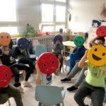 Zdjęcie grupowe w sali Ogniska, zdjęcie zrobione podczas zajęć socjoterapetycznych, dzieci mają zasłonięte twarze buziami przedstawiającymi różne miny