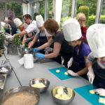 Dzieci podczas zajęć kulinarnych, a głowach mająbiałe czapki kucharskie