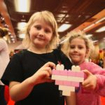 Dziewzynki na wicieczce w muzeum klocków lego trzymające serce ułożone z klocków