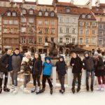 Dzieci na łyżwach na tle Starego Miasta