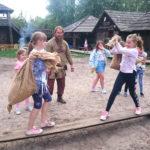 Dzieci na wycieczce w starej osadzie, rywalizacja 2 dziewczynek - test równowagi