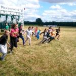 Zdjęcie grupowe, dzieci biegnące na terenie wyścigów konnych