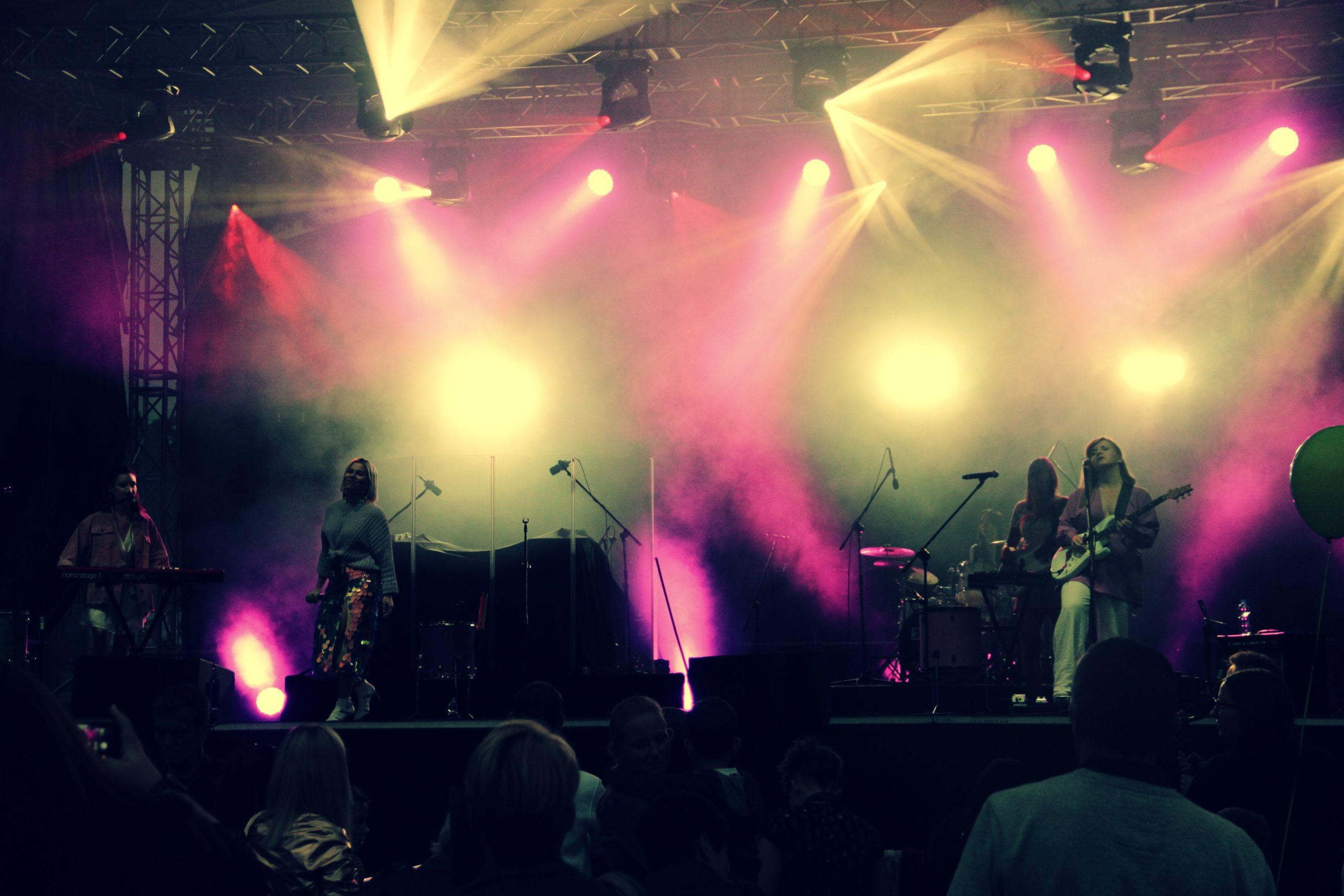Wieczorny występ zespołu Prink Girls - wykonawcy na podświetlonej scenie